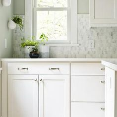 Nice backsplash - Lovely kitchen with white shaker cabinets paired with Caesarstone Frosty Carrina countertops and Boutique Oriental White Echelon Tile by Olympia Tile backsplash paired with a gray green paint color, Sherwin Williams Aloof Gray. Bright Kitchens, Home Kitchens, Eclectic Kitchen, Kitchen Decor, Kitchen Ideas, Kitchen Witch, Layout Design, Design Ideas, Diy Design
