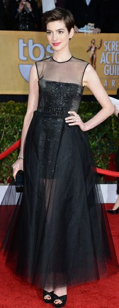 Who made Anne Hathaway's black mesh gown, black sandals, jewelry, and black glitter clutch handbag that she wore to the 2013 Screen Actors Guild Awards? Dress – Giambattista Valli  Shoes – Jimmy Choo  Jewelry – Kwiat  Purse – Eddie Parker