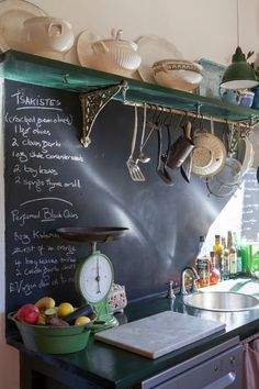 Like the blackboard, black countertop, and great shelf with lacy brackets and hanging pots.