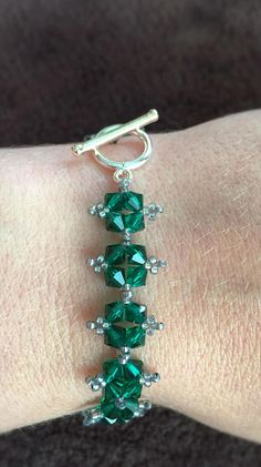 Green Swarovski Crystal Beaded Bracelet This bracelet features deep green Swarovski crystals with smoky gray seed beads and a toggle closure. Can easily be dressed up or dressed down to add sparkle to any outfit. Perfect as a holiday gift! Or buy it for yourself to wear to anytime.