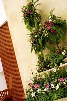 Así es como luce este altar con estas enormes y espectaculares bases todas con diferentes diseños combinado siempre unas hojas como las monsteras al igual que unas draseñas grandes y palmas en diferentes tamaños, las flores utilizadas fueron las lilis blancas combinadas con una stargeizer en color fushia todo con toque de gysophilia.