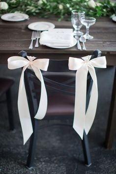 Let's have this type of ribbon on the chairs, but pink instead of white, and only one, on one side of the chairs (let's say the right one). I like the long ends of the ribbon. Would it be possible to put a white (and green stem) flower in the middle of the bow (make the bow around a flower)?