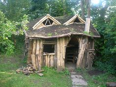 A sod-covered found-wood playhouse in a woody British backyard | Offbeat Home
