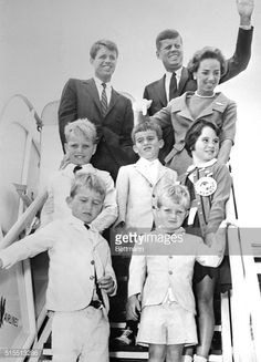 Democratic presidential nominee, John F. Kennedy waves as he boards a plane enroute to his Massachusetts home. On the ramp with Kennedy are Robert Kennedy, his brother and campaign manager Mrs. R....