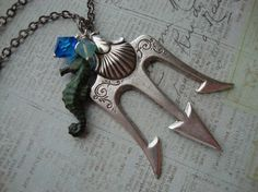 Are you a fan of the Percy Jackson books? How about The Heroes of Olympus? Be the first to have this super fun necklace representing Poseidon, the father of Percy Jackson. Armed with your mighty trident, you'll always be ready for action!  A super cool trident is adorned with a green patina sea...