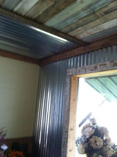 Corregated metal on front wall & ceiling sections. Recycled privacy fence on alternating ceiling sections and framing window.