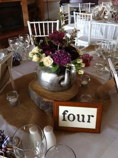 Rustic table centrepiece of wood slice with vintage kettle. Filled with sweet pea, spray roses, ranunculas, hyacinth and cymbidium orchids at Wandin Valley Estate, Hunter Valley Australia www.jademcintoshflowers.com.au