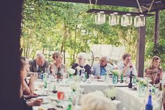 ANother picutre of the 25 guest wedding with the custom-built pergola.  I like the arrangement of 4 tables  in a square with the mason jar chandelier (or a real fancy chandelier hanging from a tree.