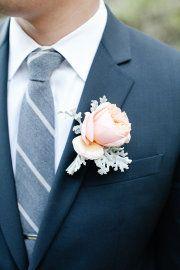 Navy suit, grey tie, peach boutonniere. Very dapper.