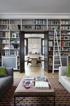 This bookshelf was designed by Sigmar, along with the ladder. It needed to house the owner's large collection of books, as well as accommodate the existing radiators. The backdrop for the interior is various grey shades, while the green and red provide bright accents. The walls and bookshelf are painted in London Cloud from the Damo collection, available at Sigmar. The woodwork is Cocoa, also from Damo. #Sigmar #shelving #livingroom http://www.sigmarlondon.com