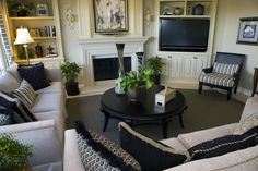 Living and family room with two sofas, round coffee table, ornate fireplace and built in shelving, one with a television.