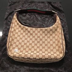 Classic Gucci Bag Classic Gucci in very good used condition. The plastic protective coating is still on the strap hardware. The strap is the classic green and red - material strap. The inside of the bag is flawless- no stains or tears. The outside of the bag is in excellent condition with the exception of a pen sized dot near the side of the bag.  More pics upon request.  Original Gucci dust bag included. Gucci Bags Shoulder Bags
