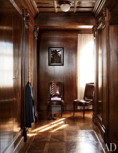 A dressing room by Roberto Peregalli and Laura Sartori Rimini is lined in walnut, with a Renaissance wood relief on the far wall.