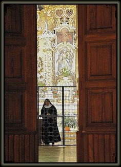 "A cloistered nun seen thru the ""grille"" or enclosure within a monastery - designed to separate the nuns from ""the world"" and to ensure that they have the environment they need for their dedication to the contemplative religious life"