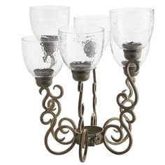 An evening of outdoor entertaining becomes a more elegant affair with the addition of this sculpted wrought iron candle holder. Uniquely designed to fit around the umbrella pole atop the patio table, the flickering light through hammered glass makes hot dogs and burgers feel like gourmet fare.