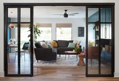 The den was previously a garage conversion that felt cold and uninviting. By bringing the same flooring in here and opening up the doorway, it automatically made this feel like it had always been part of the home. We carried the same look from the kitchen into this space with these black metal framed sliding glass doors. I love the way these kinds of doors offer privacy (and noise control with 6 kids), without shutting the space off from the rest of the home.