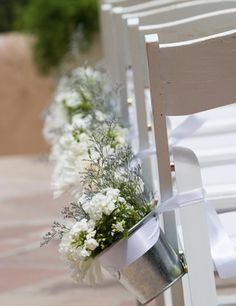 White chairs and flowers in buckets