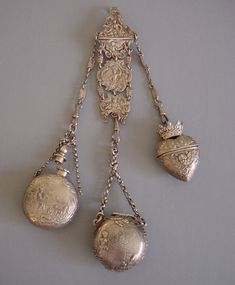 CHATELAINE  sterling  	chatelaine with embossed figural designs or cherubs on each piece,  	hallmarked 8 total length, perfume 1-5/8, vinaigrette 1-5/8, heart with  	crown pill box 1-3/4. Even the links have faces on them.