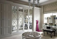 Incredible walk-in closet with wall to wall gray closets flanking mirrored…