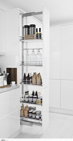 Pull out larder units are perfect to stock up on your food and grocery shop! Shelves are tall enough to stock bottles and larger cereal packages. Neat and tidy white gloss handless kitchen is now clutter free. Storage solution photography by http://capture.setvisions.co.uk/Portfolio