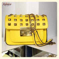 Bolsa feminina Gloss de couro amarelo, com forro de tecido, bolsas internos e alça de couro e correntes. Tampa de couro com metais.