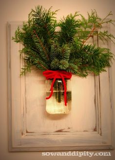 Simply Prim Christmas...fresh pine in a mason jar...tied with a red ribbon & hung on the wall.
