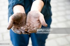 Manual labourer with dirty hands begging for money, symbolic image of an illicit worker