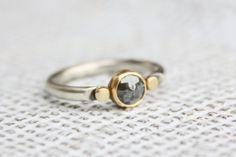 This two tone ring features a charcoal-hued round rose cut diamond in sterling silver and 14k yellow gold.  . Made by hand with eco-friendly metals and conflict-free diamond.  Details:  - handmade from .925 sterling silver and 14k gold - gray rose cut diamond measures 6mm - sterling