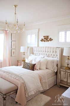 This pink and gold bedroom featuring a tufted wingback headboard by Randi Garrett Design is stunning.