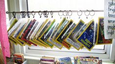 magazines displayed in page protectors and hooked onto a curtain rod with circular hooks