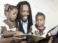Minister of State for Tourism Damion Crawford reads to Dejanea McIntyre (left) and Xarian Taylor, both students of Pentab Early Childhood Institution, in the Crayons Count learning lorry yesterday in central Kingston. The after-school event was held in the Gleaner parking lot along East Street. Participating schools were selected by the National Child Month Committee.- Gladstone Taylor/Photographer