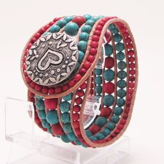 An inch and half wide 5 row cuff with a heavy duty heart button. The beads are blue turquoise and red turquoise Howlite from Turkey and the rows are made up of beads in 4mm 6mm and 8mm. Natural leather is used to give it a Southwestern style design, this is a lovely wide cuff that goes well with Western wear!  Fits a 7'' wrist snug but comfortably  $55.00
