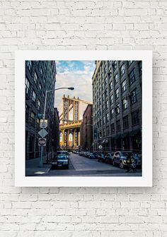 A square fine art photograph taken in New York City of the Manhattan Bridge at sunset.