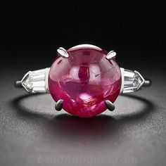 Art Deco Cabochon Ruby Platinum Diamond Ring, A gleaming candy apple-red cabochon ruby, weighing approximately 4.00 carats, glows between a pair of sleek and shimmering bullet-cut diamonds (.50 carat total weight) in this streamlined and stunning original Art Deco bauble, crafted in platinum - circa 1930.