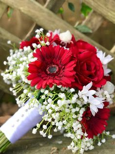 This beautiful bouquet is made from real touch red roses and gerbera daisies, highlighted with snow white baby's breath. Each bouquet that is ordered comes with a matching complimentary boutonnière. Daisy Bouquet Wedding, Gerbera Daisy Bouquet, Simple Wedding Bouquets, Red Wedding Flowers, Gerbera Daisies, Gerbera Daisy Colors, Gerbera Daisy Centerpiece, Prom Bouquet, Homecoming Flowers
