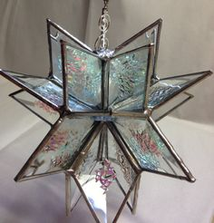 This is a stained glass dichroic bevel star or snowflake suncatcher is made up of many ice dichroic bevels. The bevels are offset with a polished