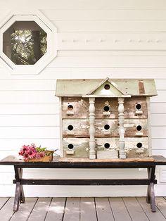 An antique birdhouse adorns the porch at this sprawling New York garden estate.