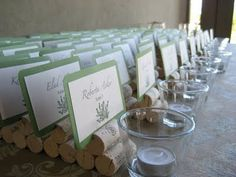 Our wedding idea. We used corks and slit the top of them to put the place cards in. The center piece was then a bottle of wine with our pictures on it!