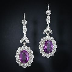 A pair of richly colored oval sapphires, together weighing carats, display a deep lavender-pink hue and glow from sparkling scalloped frames of old mine-cut diamonds surmounted by diamond-set leaf motif pendants. These gorgeous, vintage drop earrings Pink Sapphire Earrings, Diamond Drop Earrings, Sapphire Jewelry, Gemstone Earrings, Diamond Jewelry, Purple Diamond, White Gold Diamonds, Sapphire Diamond, Diamond Art