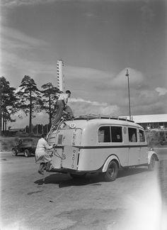 Broadcast van outside the Olympic Stadium in Helsinki, ca. 1937. Ensimmäinen Yleisradion ääniauto vuodelta 1937 Helsingin Olympiastadionin ulkopuolella, työntekijät kiipeävät auton katolle, taustalla stadionin torni. Kuvausaika arvioitu vuoden tarkkuudella.