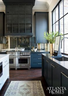 White and black kitchen features black cabinets paired with honed black granite countertops fitted with a stainless steel sink and a sleek black faucet placed under a bank of steel windows.
