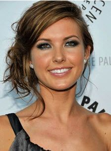Dark brown straight hair with a loose low curly side bun updo and a deep side part hairstyle