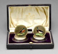 LOT:515 | An Edwardian cased pair of silver and enamel game bird menu holders.
