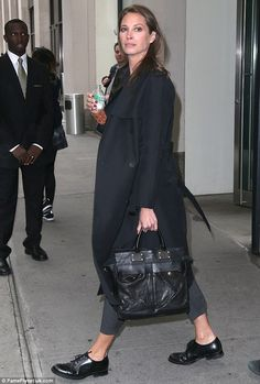 Model behavior: Christy Turlington, looks effortlessly chic in a classic long black trench coat with grey cigarette-style pants, black brogue shoes and a fresh red manicure while carrying a Rag & Bone pilot bag in New York City on Thursday Brogues Outfit, Oxfords, Vogue, Christy Turlington, Mode Inspiration, Look Chic, Looks Style, Facon, Mode Style