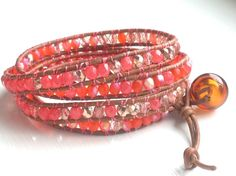 This pretty coral and pink bohemian chic leather wrap bracelet features a light brown hollow lampwork glass bead closure, 4mm pink dipped (coated) czech