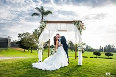 San Diego wedding at lomas santa fe country club bride strapless tulle ball gown with beaded bodice and purple sash with groom navy blue suit with matching vest and white dress shirt with white bow tie and white floral boutonniere kissing in front of altar