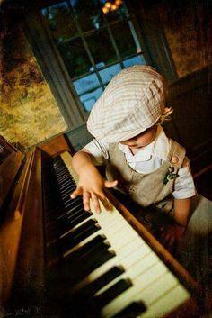 Egy kisfiú próbál játszani a nagy zongorán.