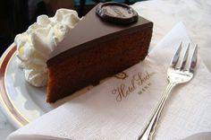 Sachertorte, Viena, Áustria Sabe o que te espera em Viena? Um pão de ló de chocolate revestido manualmente com geleia de damasco e cobertura de chocolate escuro. O doce típico foi criado em 1832 por Franz Sacher para impressionar seu empregador na época, Klemens Wenzel, o príncipe von Metternich.Em 1876, seu filho Eduard abriu oHotel Sachercomum café esplêndido e boas lojas.