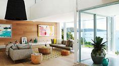séjour moderne lumineux aménagé avec deux canapés gris, deux tables basses en bois massif et un revêtement mural en bois