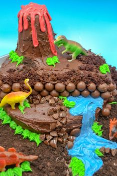 Homemade Dinosaur Birthday Cake a dinosaur birthday cake with chocolate frosting, a volcano, a blue frosting waterfall, and toy dinosaurs on a blue background Dinosaur Cakes For Boys, Make A Dinosaur, Dinosaur Birthday Cakes, 4th Birthday Cakes, Dinosaur Party, Birthday Ideas, Blue Frosting, Chocolate Frosting, Cake Chocolate